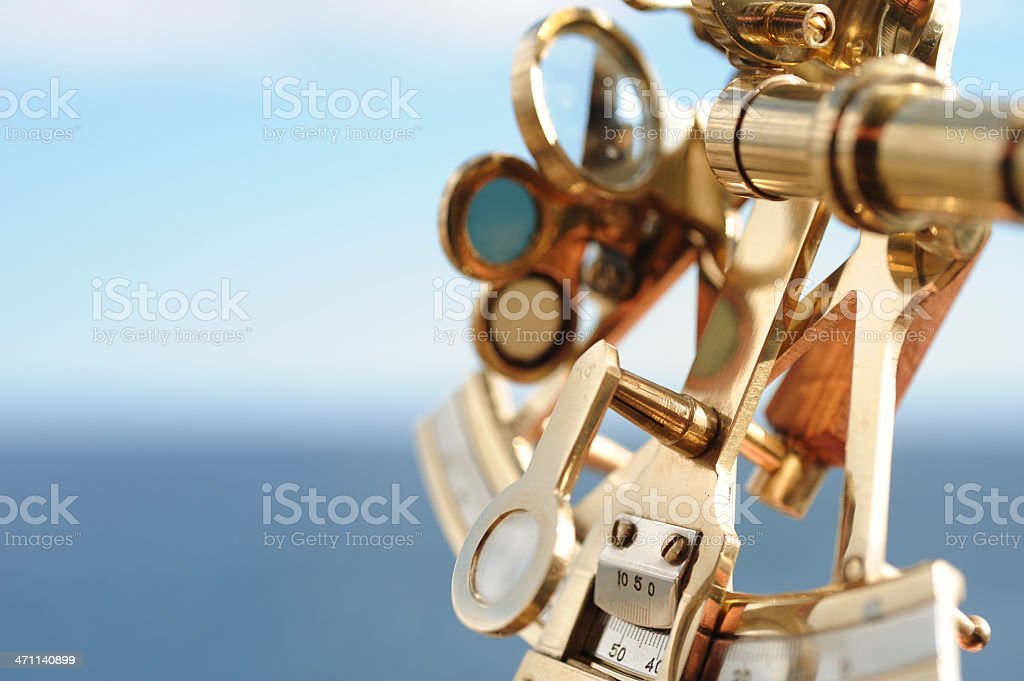 Closeup view of golden sextant with blurred sea background stock photo