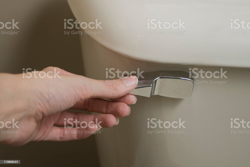 Close-up view of hand about to flush handle of tan toilet stock photo
