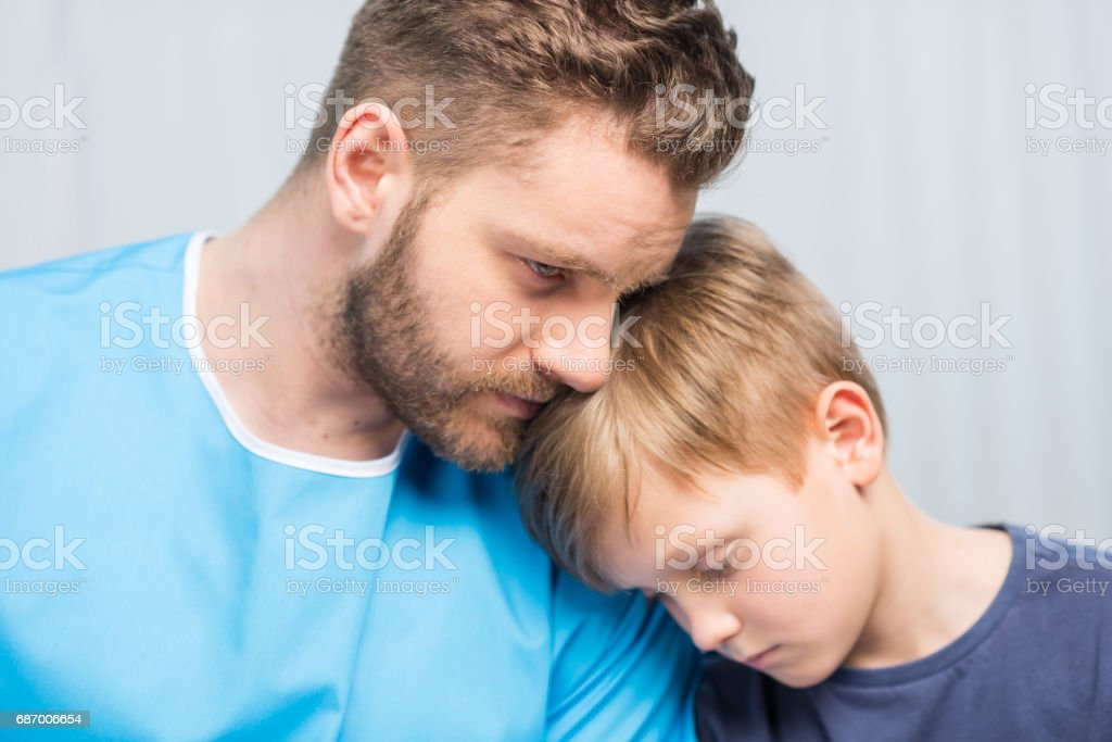 Close-up view of sick father and upset son together, dad and son in hospital stock photo