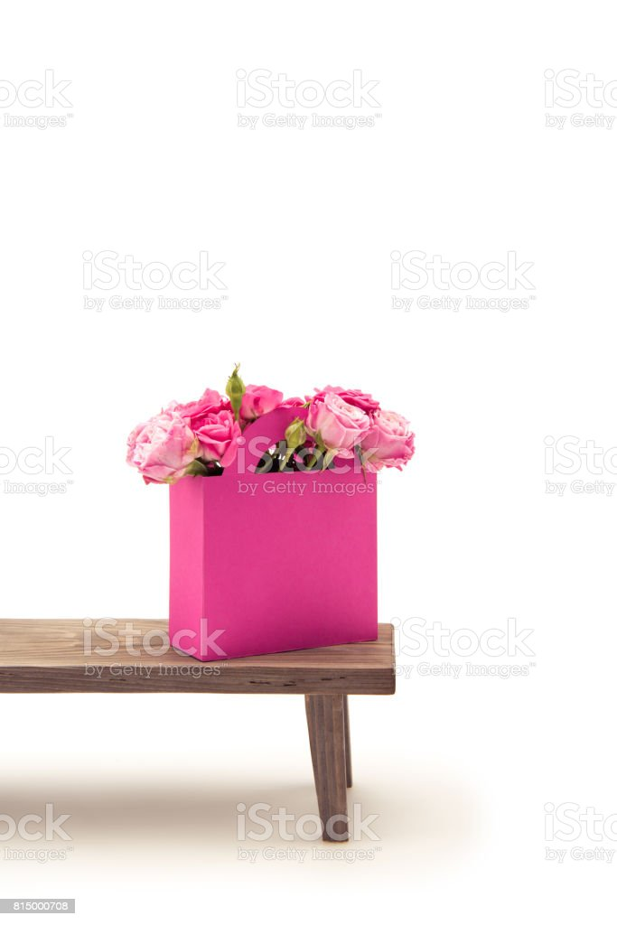 Close-up view of tender blooming rose flowers in pink paper bag on wooden bench isolated on white stock photo