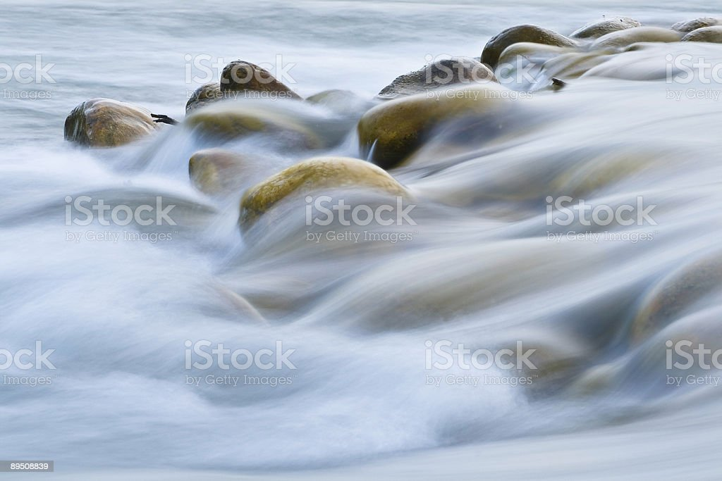 A close-up view of water flowing over stones stock photo