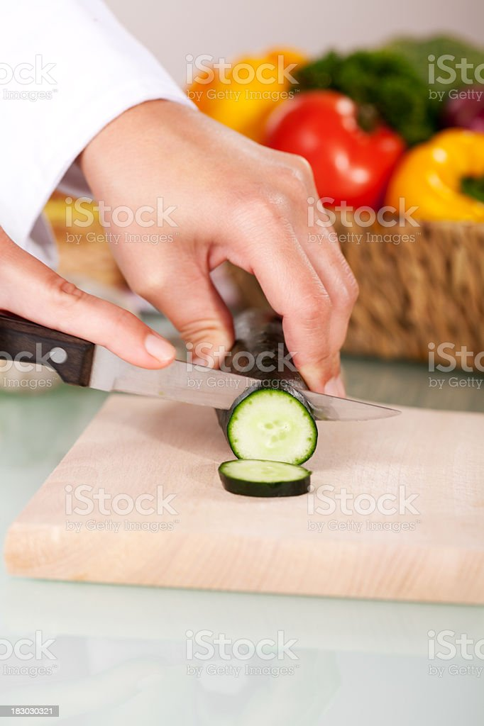 Close-up view oh chef's hand cutting cucumber with knife stock photo