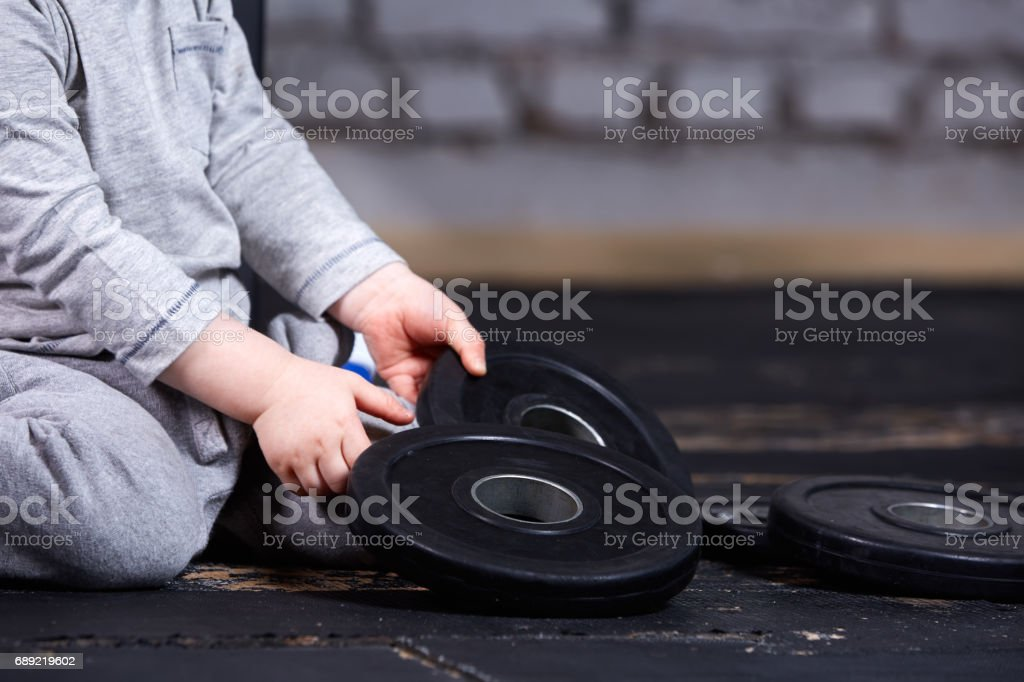 Close-up view photo of little sporty child with barbbell against brick wall at the    gym. stock photo