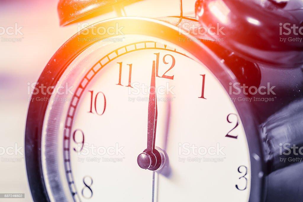 closeup vintage clock focus at 12 o'clock with sun light stock photo