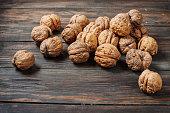 Closeup walnuts on wooden dark table.