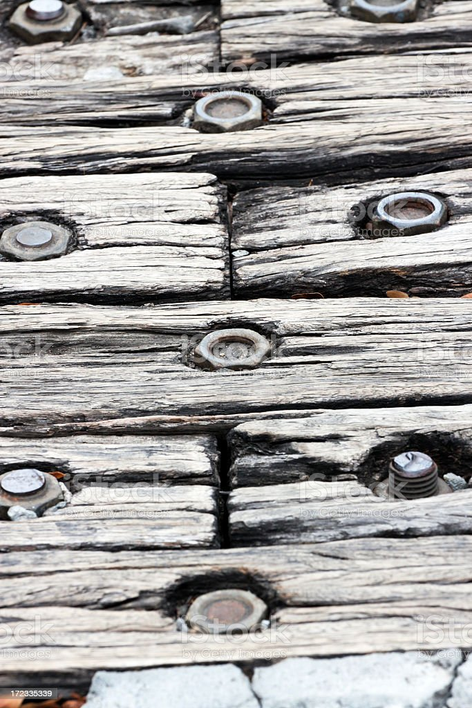 Closeup weathered wooden sleepers with rusty nuts and bolts royalty-free stock photo