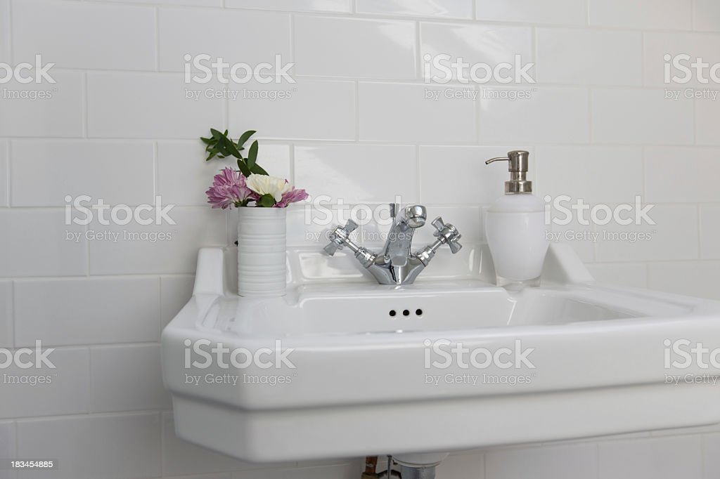 Close-up white bathroom sink with flowers stock photo