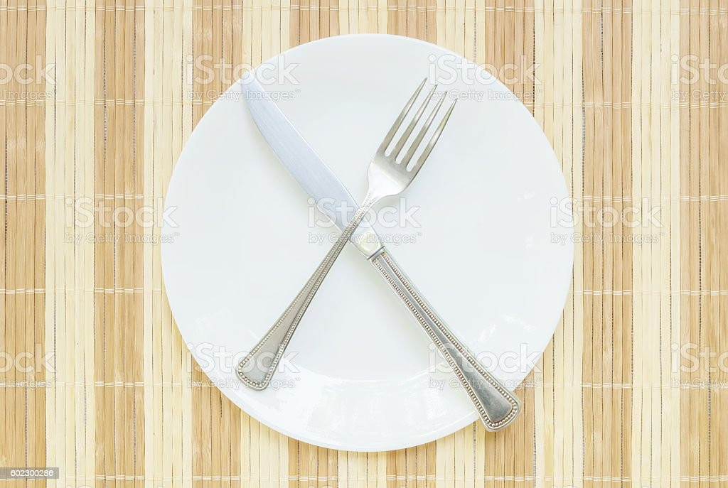 Closeup white ceramic dish with stainless fork and knife stock photo
