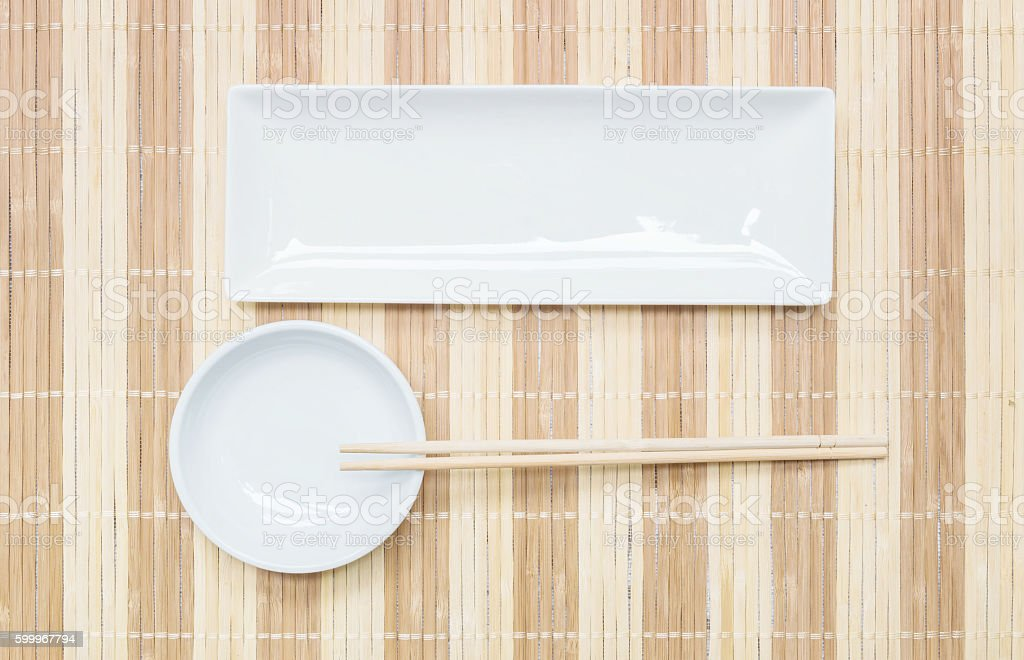 Closeup white ceramic square dish and chalice with chopsticks stock photo