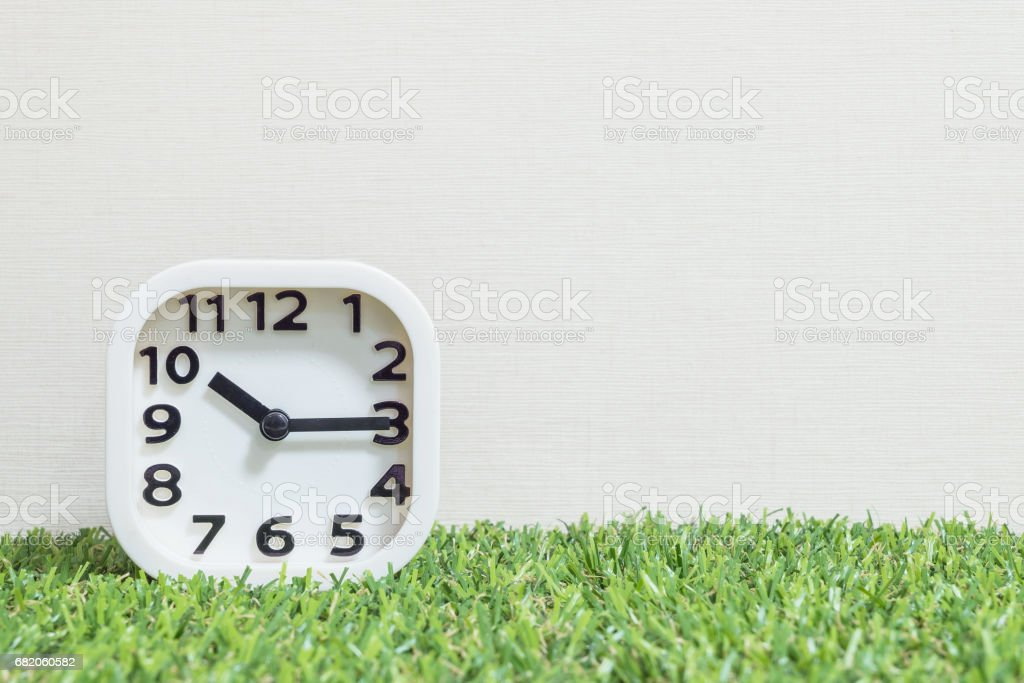 Closeup white clock for decorate show a quarter past ten or 10:15 a.m. on green artificial grass floor and cream wallpaper textured background with copy space stock photo