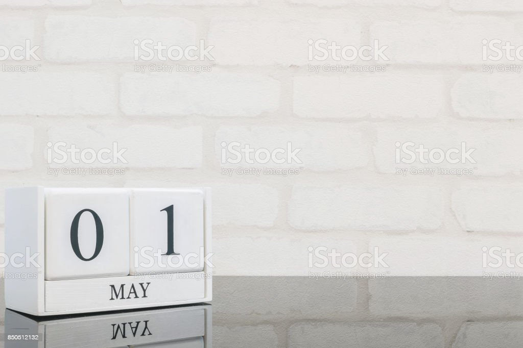 Closeup white wooden calendar with black 1 may word on black glass table and white brick wall textured background with copy space , selective focus at the calendar stock photo