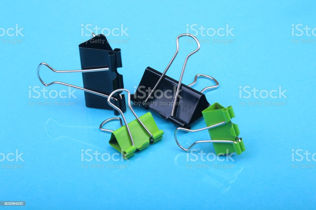 Close-up with Set of color clerical clips for paper on blue background. stock photo