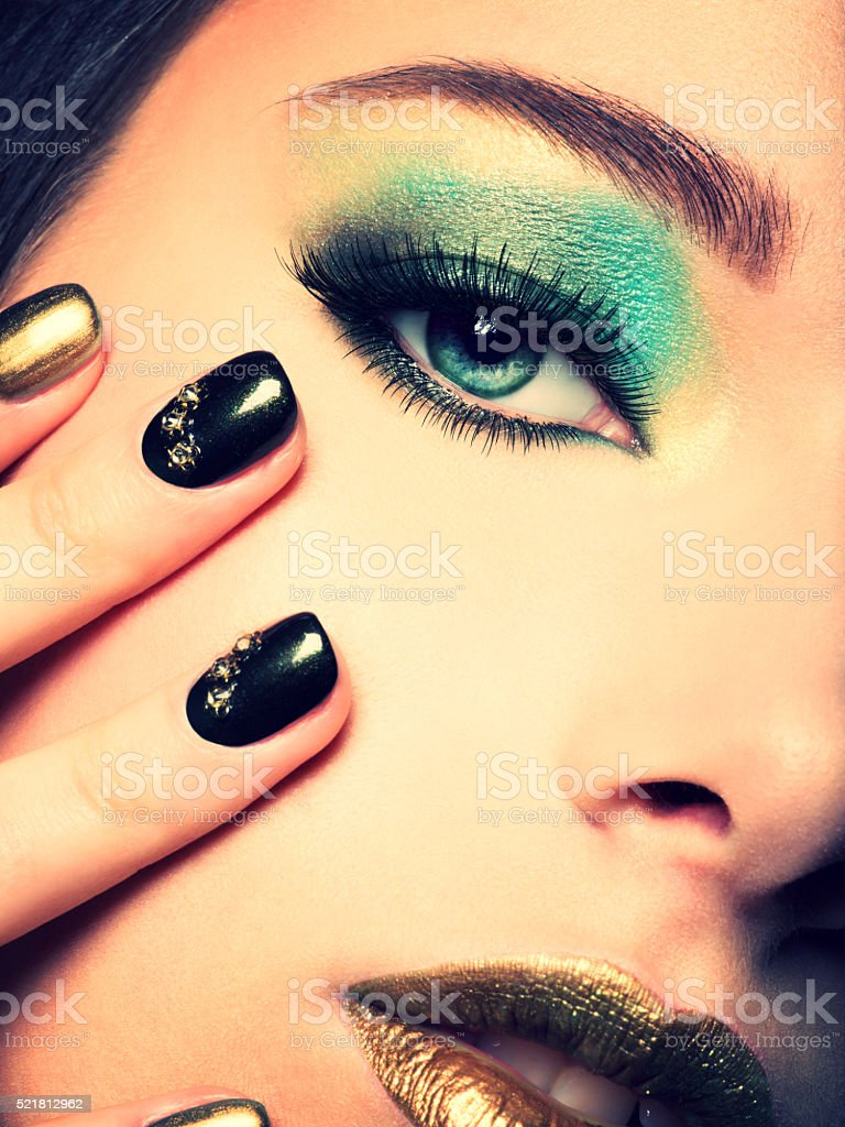 Close-up woman face with green eye make-up stock photo