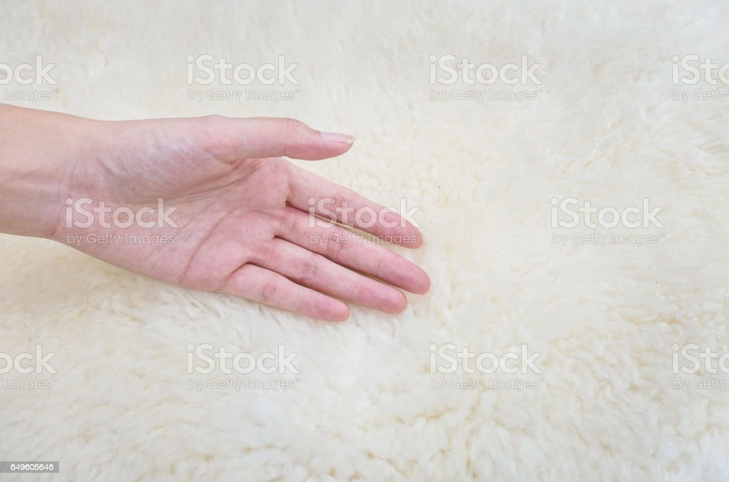 Closeup woman hand on white fabric carpet made from wool textured background stock photo