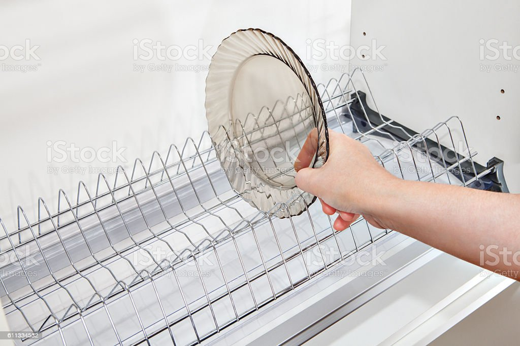 Close-up woman hand takes dish from inside wire plate drainer. stock photo