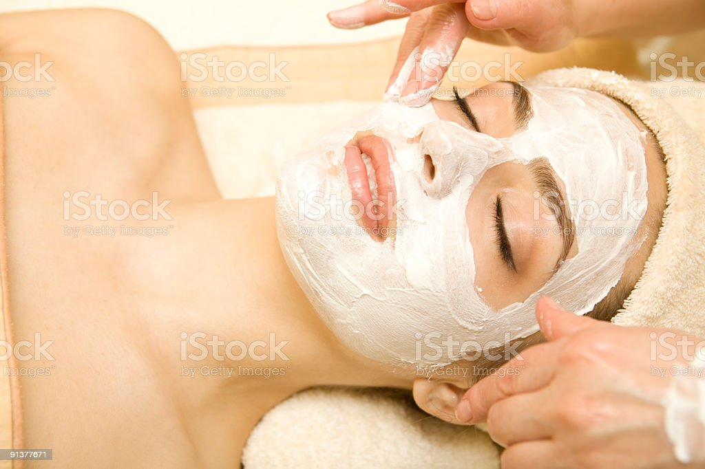 Close-up woman laying hair in towel white mask spa facial stock photo