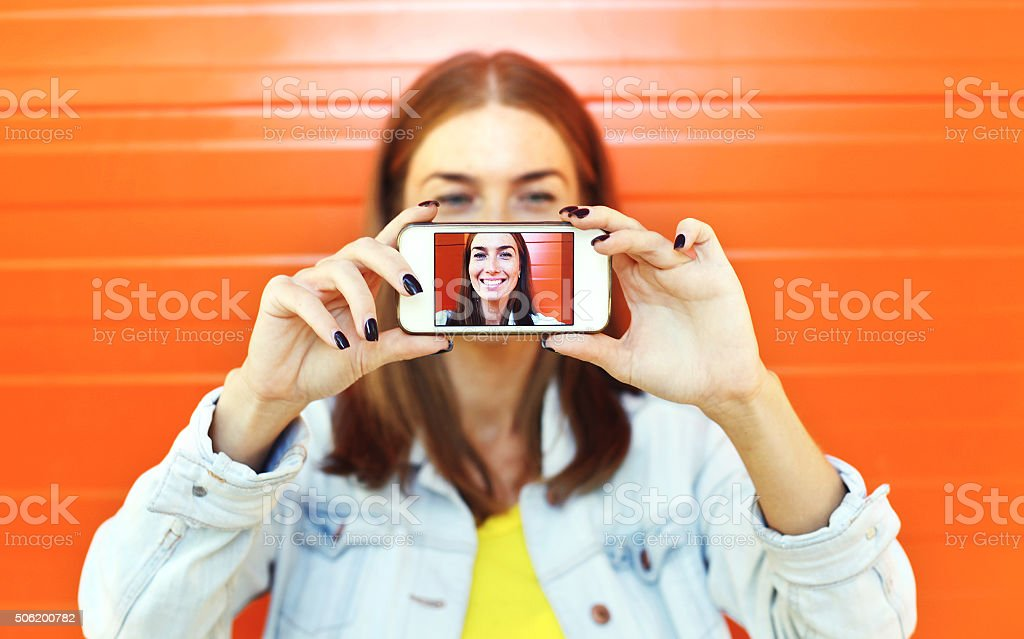 Closeup woman makes self-portrait on smartphone, view of screen stock photo