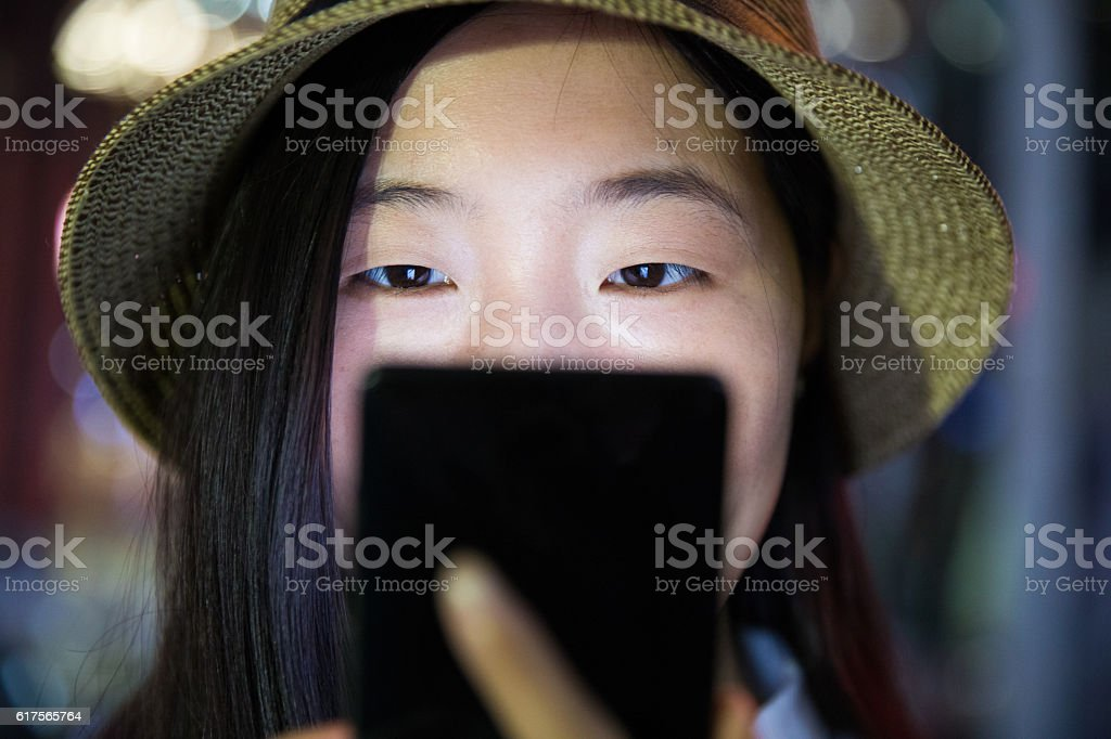 close-up woman using mobile at night stock photo