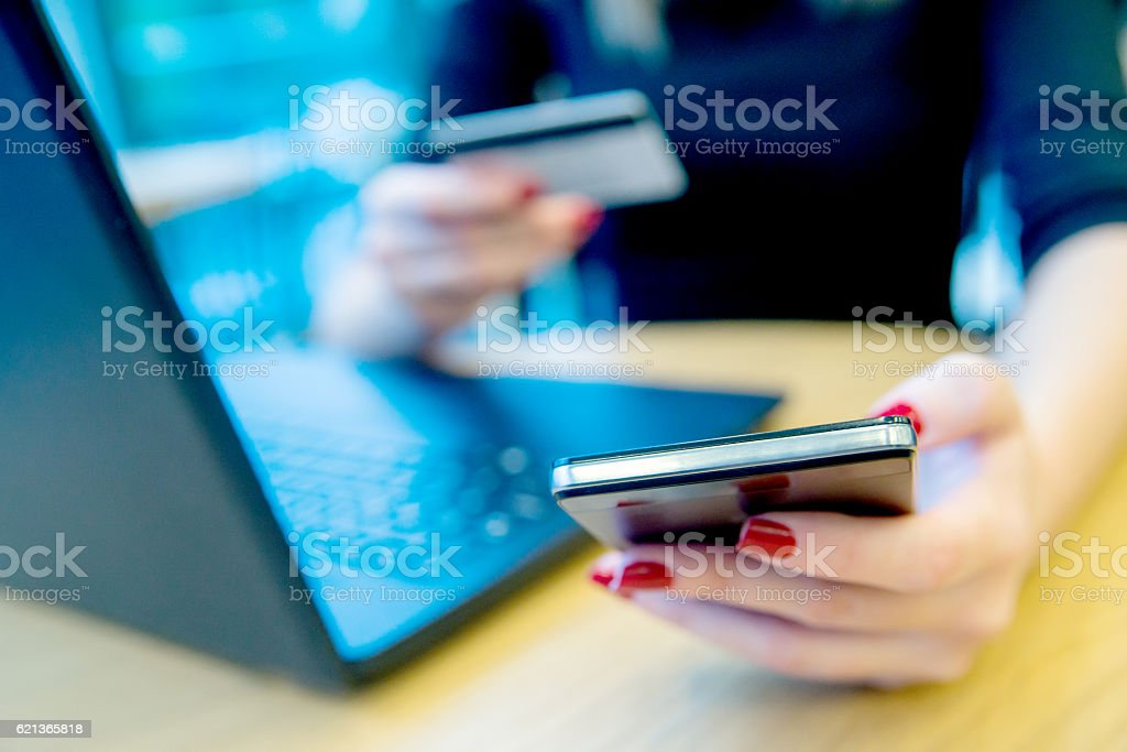 Close-up woman's hands holding a credit card and smartphone stock photo