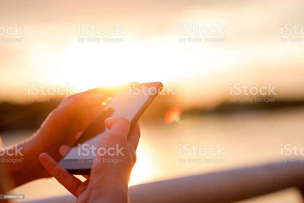closeup women using smartphone at sunset stock photo