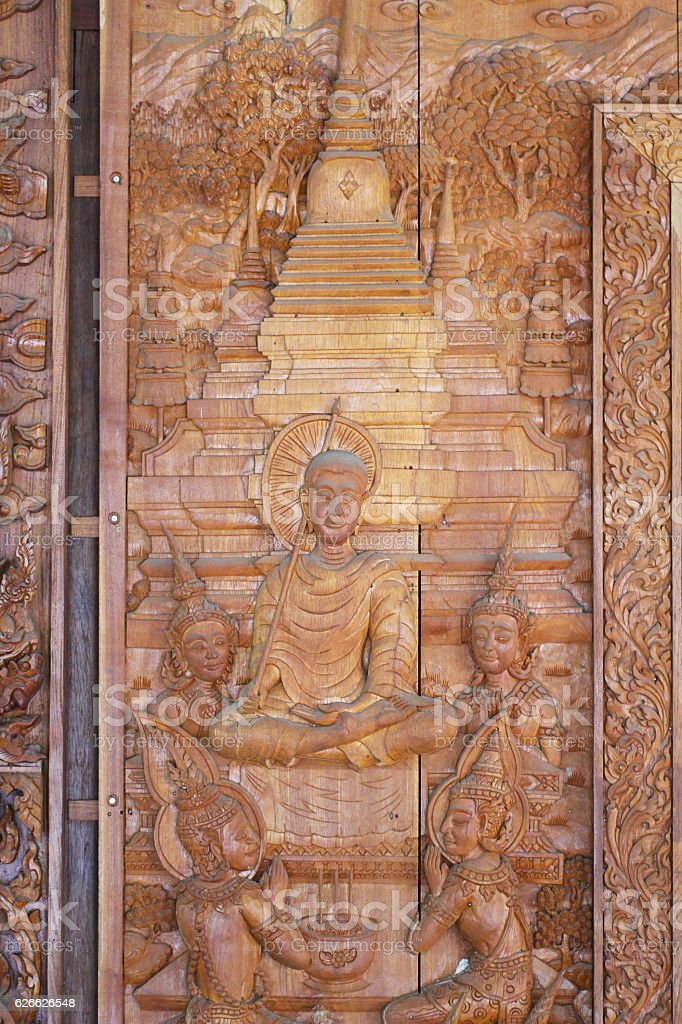 close-up wooden carving of seated buddha and temple stock photo
