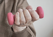 closeup wrinkled hand of a senior person holding dumbbell