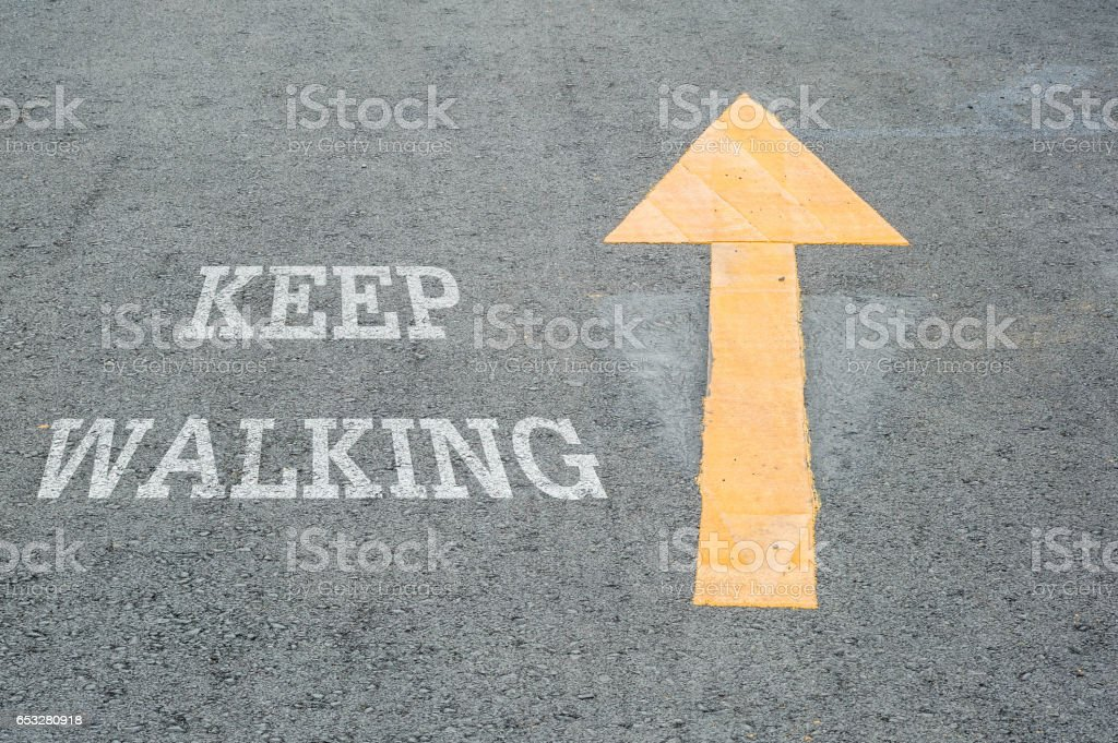 Closeup yellow painted arrow sign on cement street floor with white keep walking word textured background stock photo