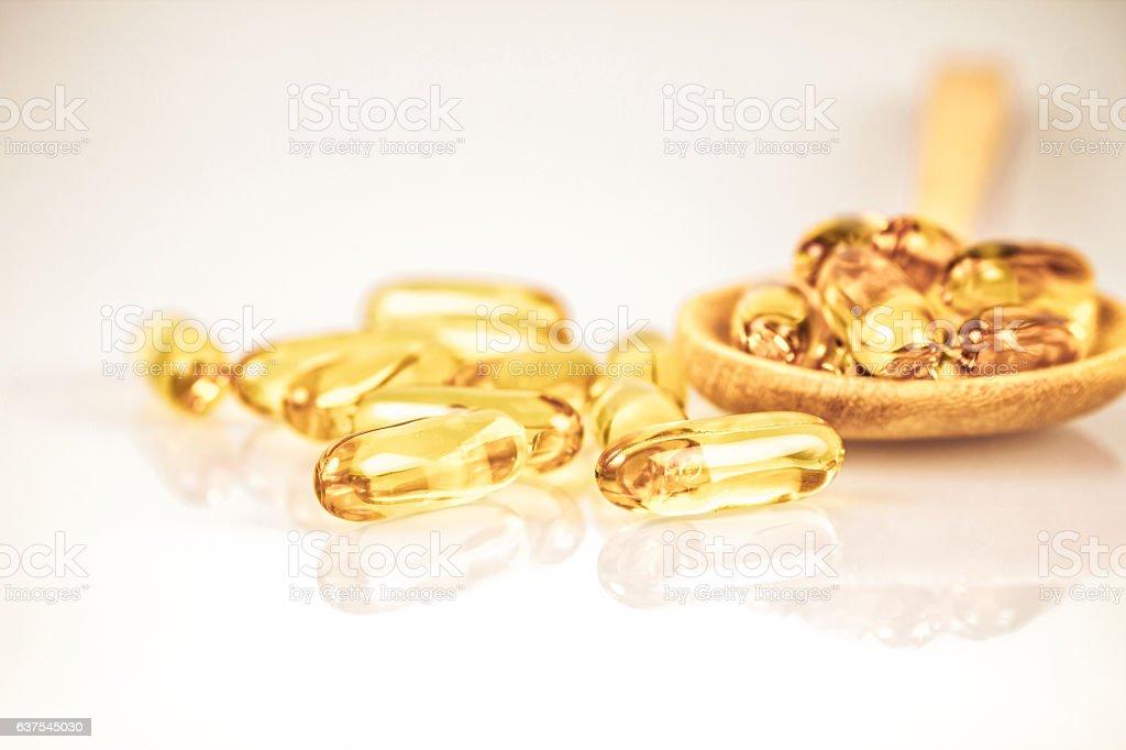 Closeup yellow soft gelatin supplement fish oil capsule stock photo