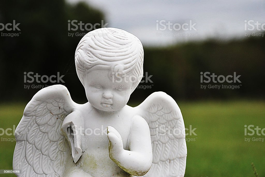 Close-Up-of-Broken-Ceramic-Cherub-Statue stock photo