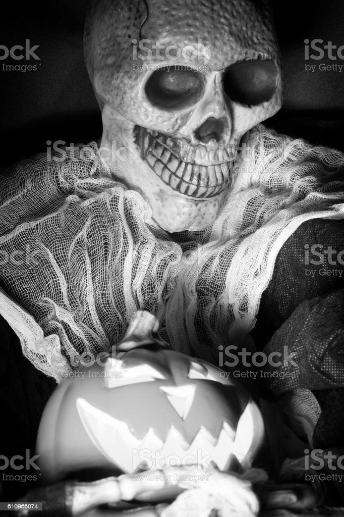 Clothed Skeleton Holding Jack O' Lantern stock photo