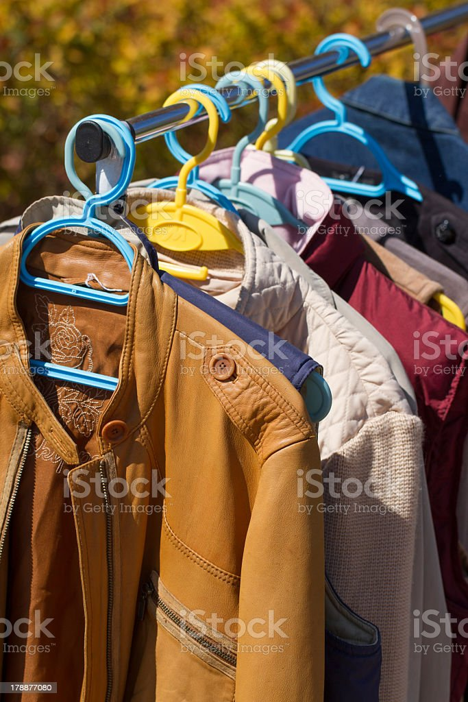 clothes and leather jacket displayed at garage sale royalty-free stock photo