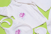 Clothes for newborn baby girl on light green background.