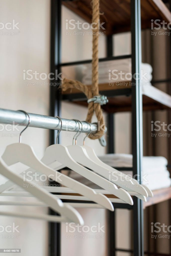 Clothes hangers on iron tube in trendy hotel room. stock photo