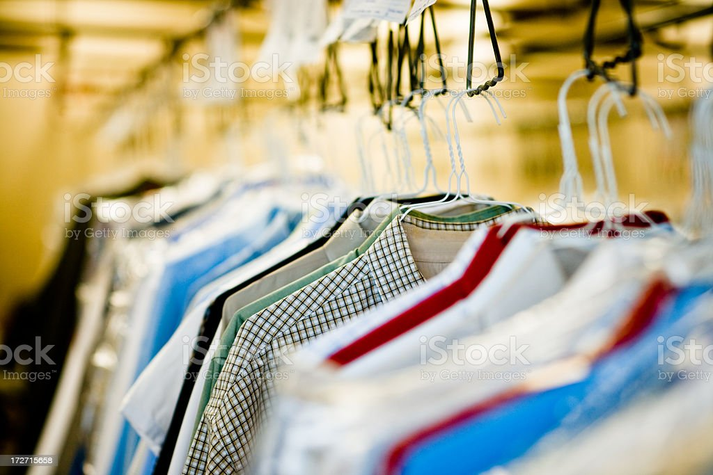 clothes hanging at dry cleaners stock photo