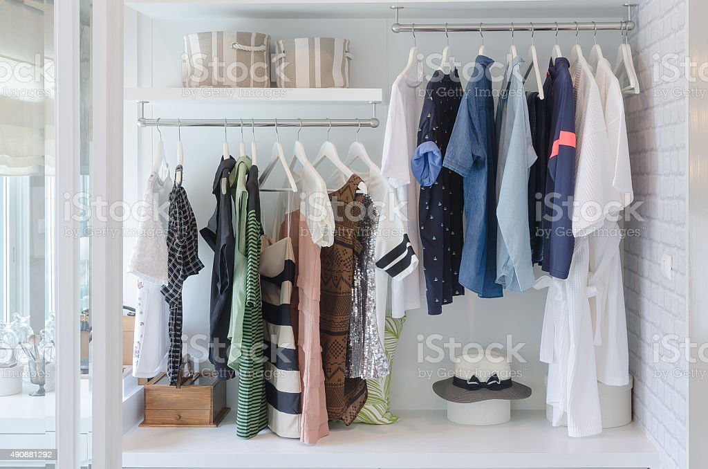 clothes hanging in closet with hat stock photo