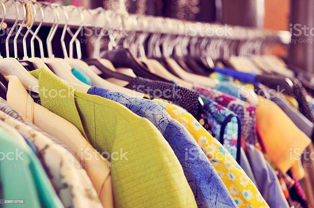 clothes hanging on a rack in a flea market stock photo