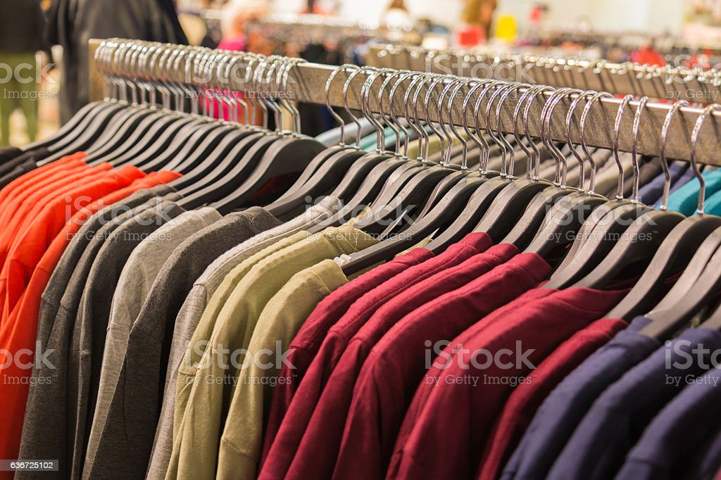 Clothes hanging on a rack in a shopping mall. stock photo