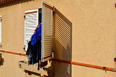 clothes hanging on a shutter of a south french building