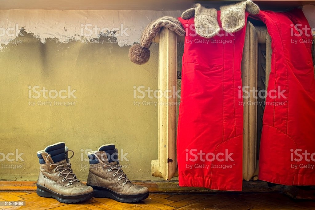 Clothes hanging on warm old radiator, beside which stands shoe stock photo