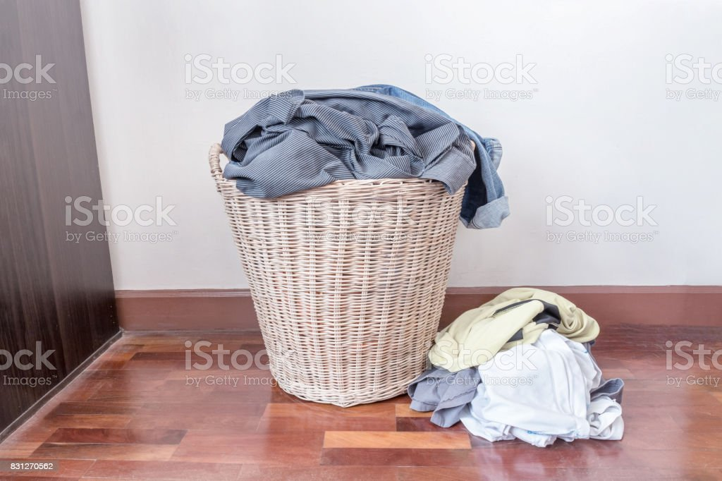 Clothes in a laundry wooden basket.The dirty clothes are not washed out of the basket. stock photo