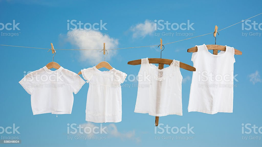 clothesline with vintage white toddler chemises stock photo