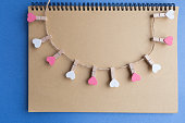 Clothespins with hearts are Notepad. Background blue paper