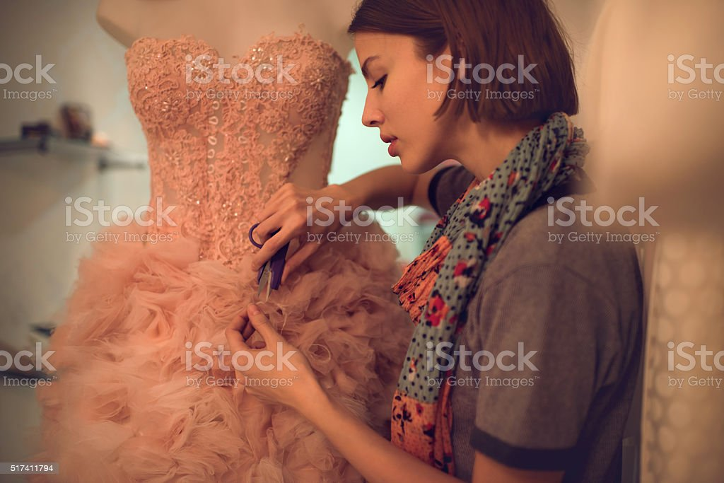 Clothing designer cutting material on a dress in workshop. stock photo