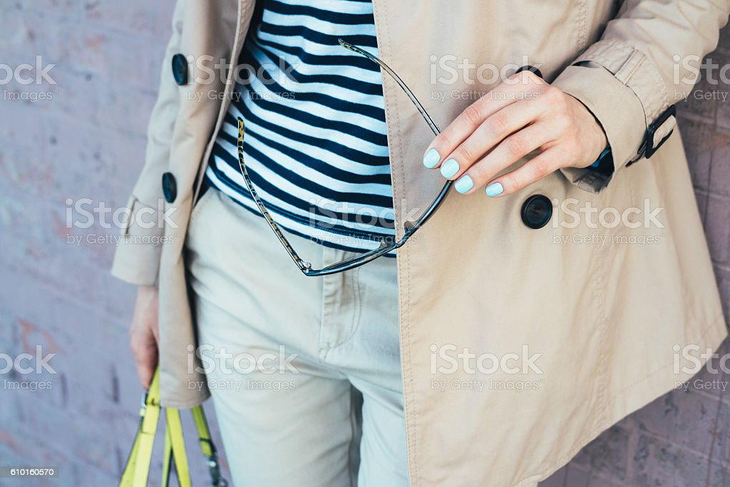 Clothing Details: woman in beige coat holding sun glasses stock photo