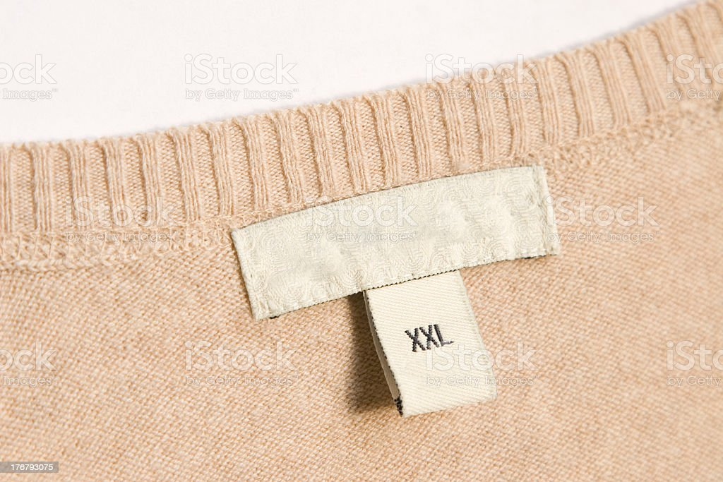 A clothing label that says XXL on a tan sweater stock photo