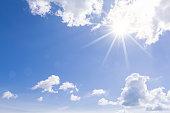 Cloud and sunburst in clear blue sky