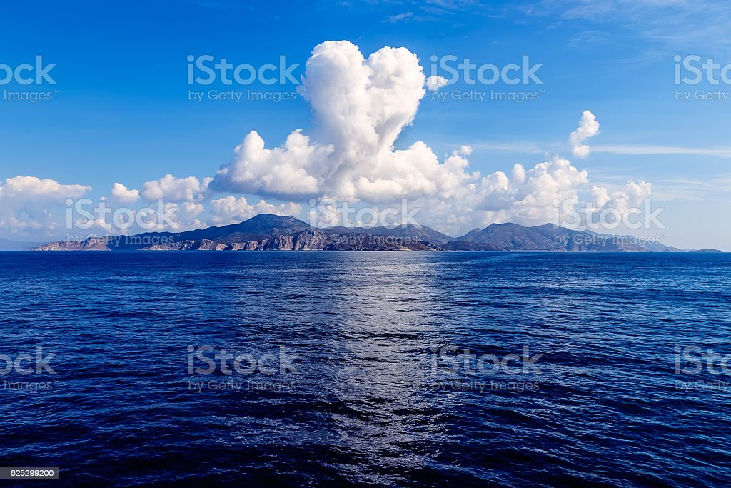 cloud in shape of heart over island in sea stock photo