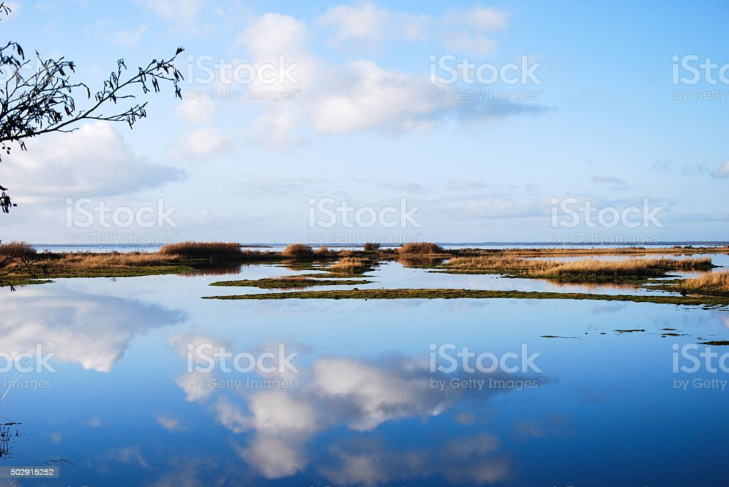 Cloud reflections in calm water stock photo