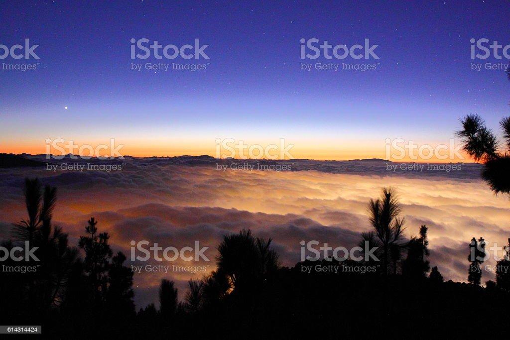 Cloud sea illuminated with city lights stock photo
