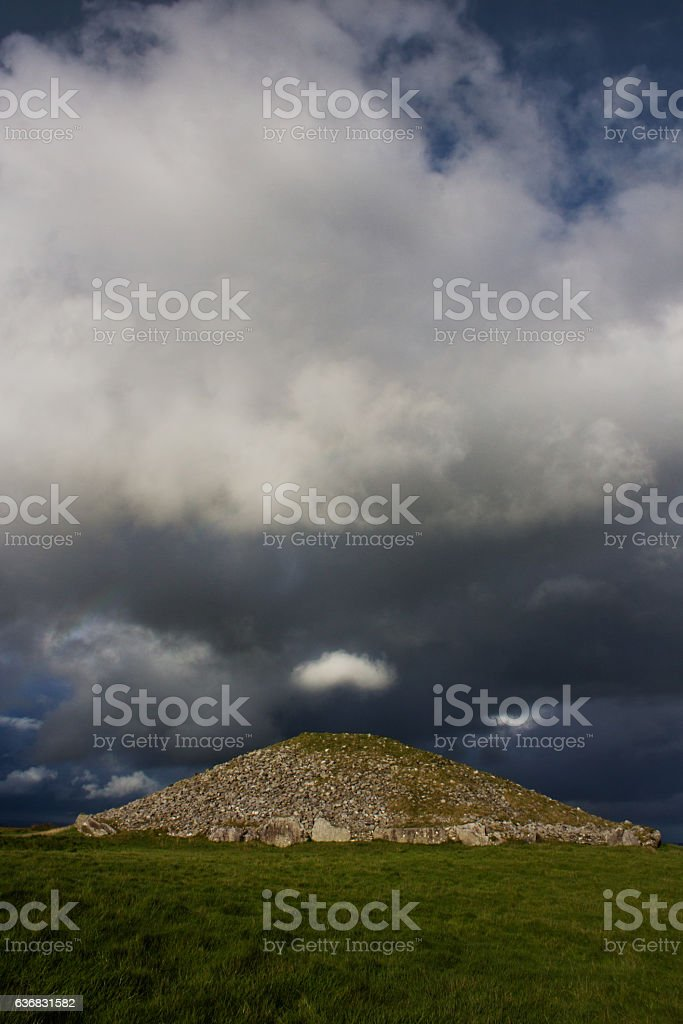 Cloud tuft over ancient passage tomb stock photo